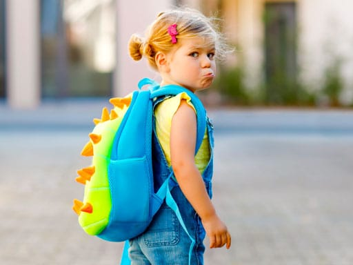 Child With Schoolbag Looking Backwards